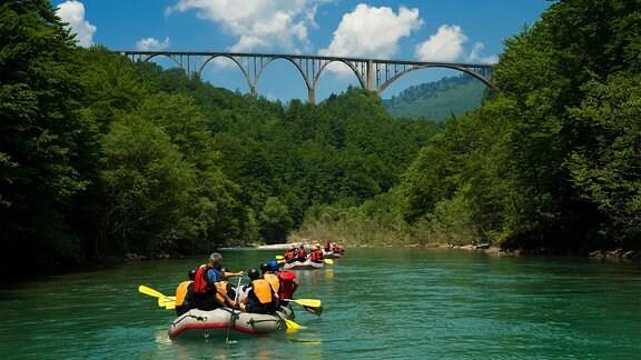 Schlauchboote auf einem Fluß, Eisenbahnbrücke im Hintergrund