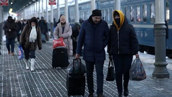 Reisende auf einem Bahnhof