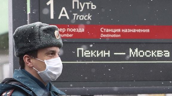 Ein Polizist in einer Gesichtsmaske am Jaroslawski-Bahnhof vor der Ankunft eines Zuges aus Peking, China