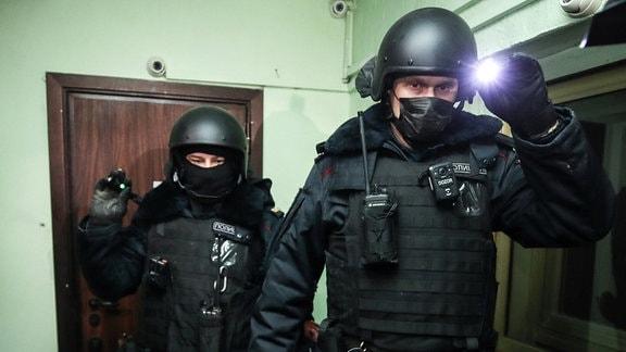 Polizisten in Helmen mit Lampe bei Durchsuchung von Wohnung von Nawalny in Moskau