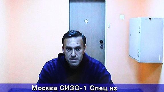 Alexej Navalny sitzt an einem Tisch in einer kleinen Zelle. Das Bild stammt offenbar von einer Überwachungskamera.