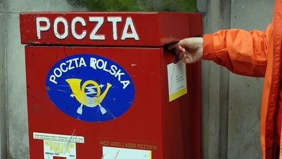 Ein roter Briefkasten mit polnischer Aufschrift.