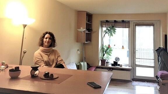 Eine Frau sitzt an einem Tisch.