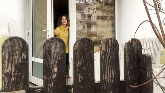 Eine Frau steht an einer Tür.