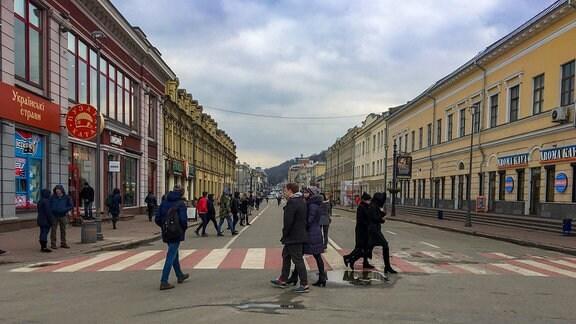 Menschen laufen über einen Zebrastreifen