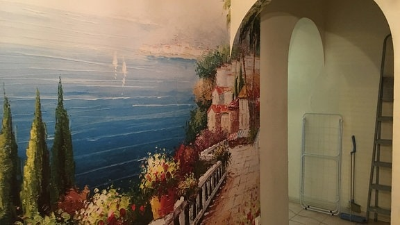 Ein Flur mit einem mediteranen Bild an der Wand