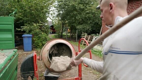 Junger Mann schaufelt Sand in einen Betonmischer.