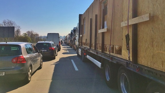 Stau auf der Autobahn. Rechts LKWs, links PKWs.