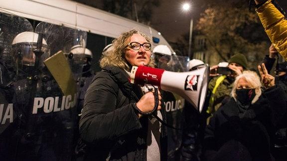 Eine Frau hält ein Megafon in der Hand.