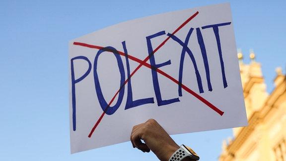 Durchgestrichenes Polexit-Schild wird hochgehalten.