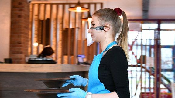 Eine Kellnerin mit Mundschutz