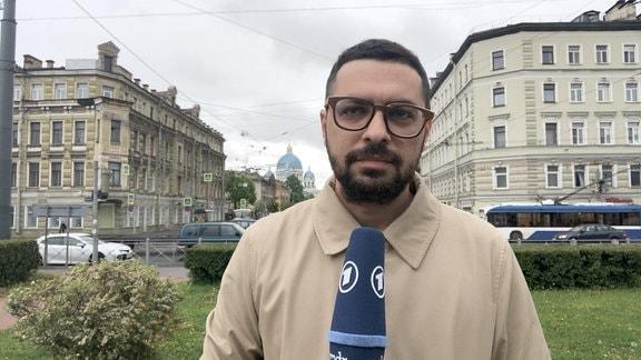 Mixim Kireev mit Mikro in der Hand an Straßenkreuzung in St. Petersburg