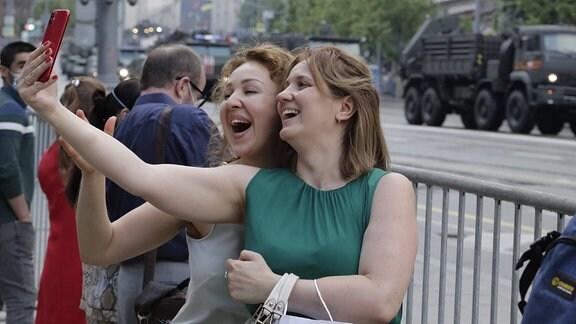 Zwei Frauen machen ein Selfie auf der Übung zur Militärparade in Moskau.