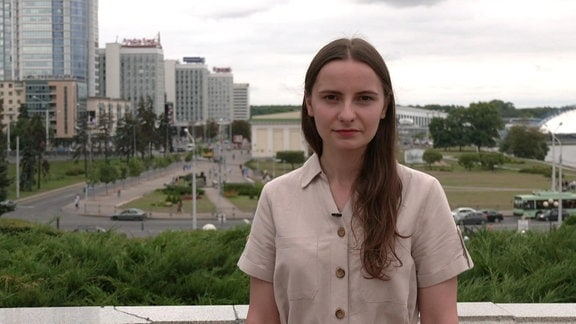 Junge Frau auf Dachterrasse vor Stadtkulisse von Minsk