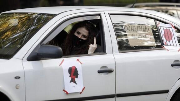 Frau im Auto zeigt den Mittelfinger