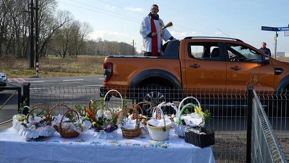 Der katholische Priester Dariusz Kiljan segnet von der Ladefläche eines Pick-ups aus Osterkörbe während der Feierlichkeiten am Karsamstag.