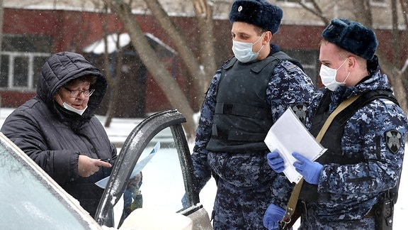 Zwei Polizisten mit Mundschutz kontrollieren in Moskau eine Autofahrerin