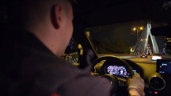 Ein Autofahrer fährt durch das nächtliche Warschau.