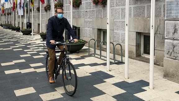 Der neugewählte Bürgermeister von Timisoara (Rumänien), Dominic Fritz, mit Mundschutz auf dem Fahrrad