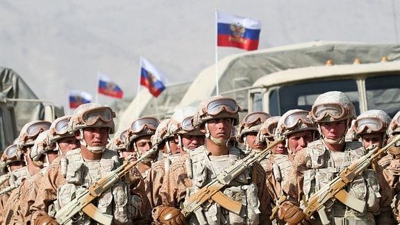Russische Truppen während Aufstellung neben russischer Fahne, im Hintergrund stehen Panzer.