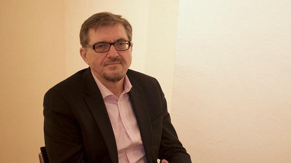 Ein Mann sitzt vor einer Wand