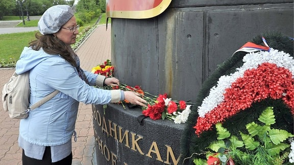 MURMANSK, RUSSIA - JULY 3, 2019: People bring flowers to a Navy memorial at the Church of the Saviour on Waters to commemorate 14 Russian Navy officers who died in a fire on a research deep-sea submersible in Russia s northern territorial waters on 1 July 2019.