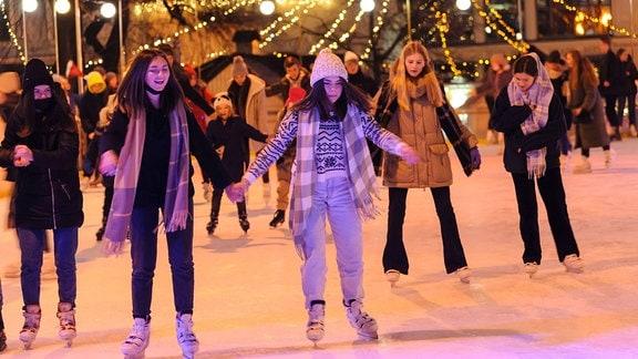 Mädchen laufen Schlittschuh auf weihnachtlich dekorierter Eisfläche