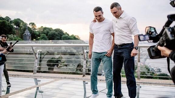 Vitali Klitschko und sein Bruder Wladimir stehen auf einer Brücke.