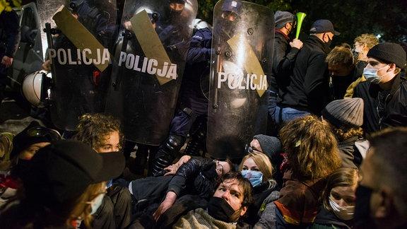 Demonstranten liegen vor Polizisten auf dem Straßenpflaster