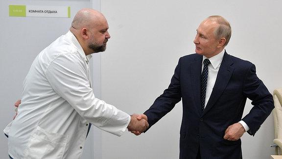 Wladimir Putin schüttelt einem Mann die Hand