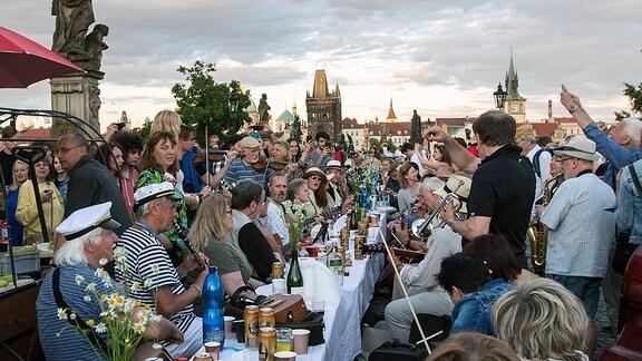 Menschen feiern in Prag auf der Karlsbrücke mit einem Abendessen an einer 500meter langen Tafel.