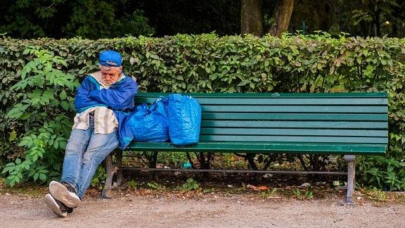 Obdachloser auf einer Parkbank