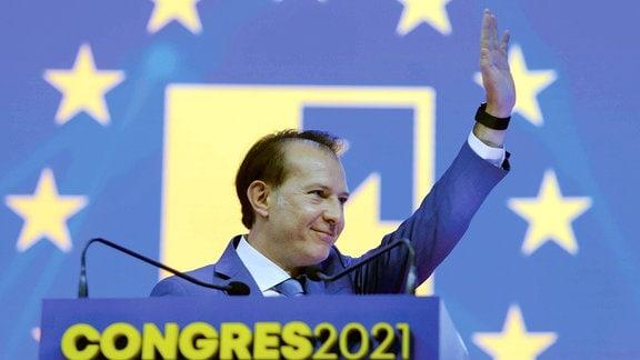 Mann hebt die Hand und winkt an einem Rednerpult, dahinter die Sterne der EU-Flagge - Rumänischer Premier beim Parteitag der PNL am 26. September in Bukarest.