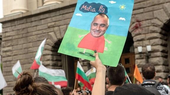Plakat mit dem Gesicht von Premierminister Bojko Borissow, gehalten von einem Demonstranten während der Demonstration.