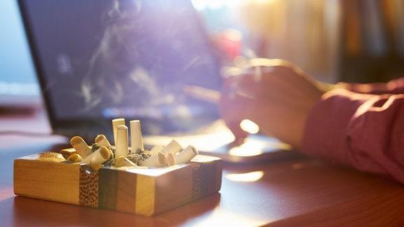 Ein Aschenbecher vor einem Laptop an dem jemand sitzt und raucht