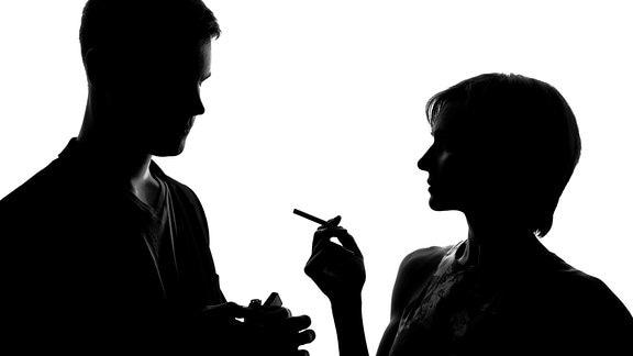 Ein Mann zündet einer Frau eine Zigarette an