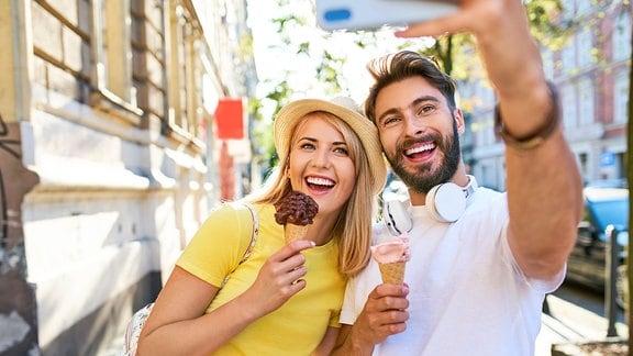 Glückliches Paar nimmt ein Selfie auf, während es Eis isst.