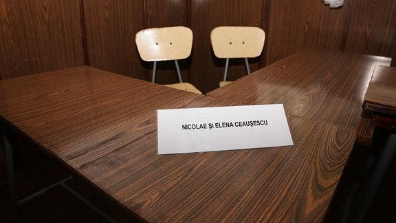 Prozesssaal - An diesem Tisch saßen am 25. Dezember 1989 die beiden Angeklagten Nicolae und Elena Ceausescu im Raum einer Militärkaserne im rumänischen Targoviste, Namensschild auf Tisch mit zwei Stühlen