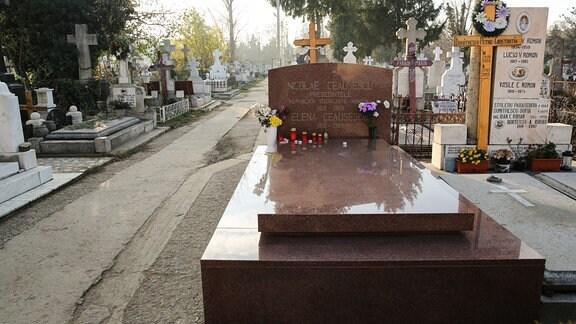 Grab von Nicolae und Elena Ceausescu auf dem Ghencea-Friedhof in Bukarest (roter Grabstein neben Gräbern aus weißem Marmor)