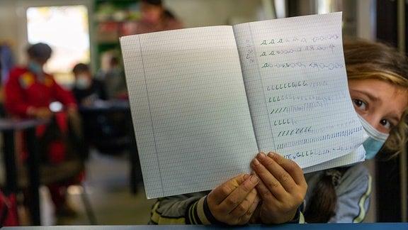 Schülerin mit Schreibheft in Rumänien