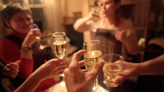 Drei Hände stoßen mit Sektgläsern an. Im Hintergrund sind unscharf zwei ebenfalls trinkende Frauen in einem hell erleuchteten Raum zu erkennen.