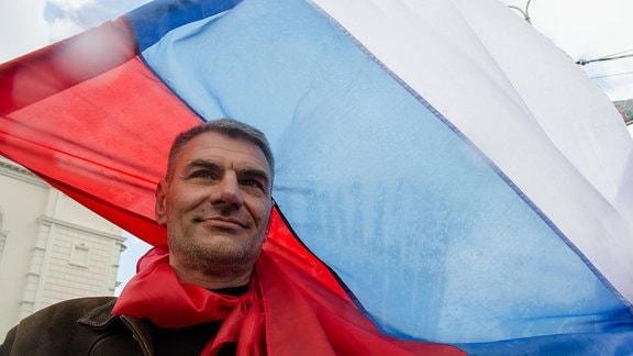 Mann trägt russische Fahne