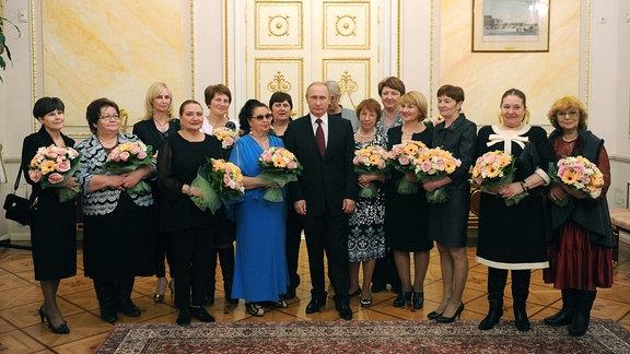 Putin mit einer Gruppe Frauen, die Blumensträuße halten