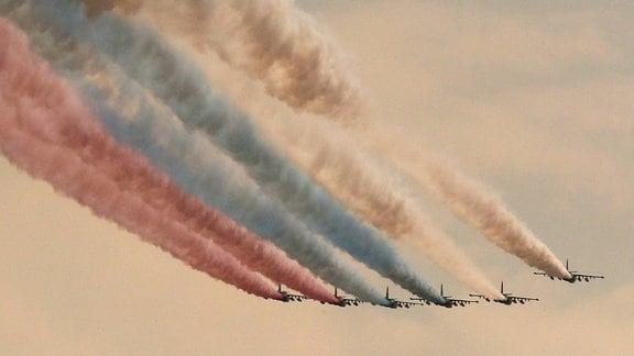 In Formation fliegende Flugzeuge hinterlassen Kondensstreifen in den Nationalfarben Russlands.