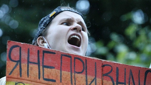 Ein Protestteilnehmer hält ein Schild hoch und ruft etwas.