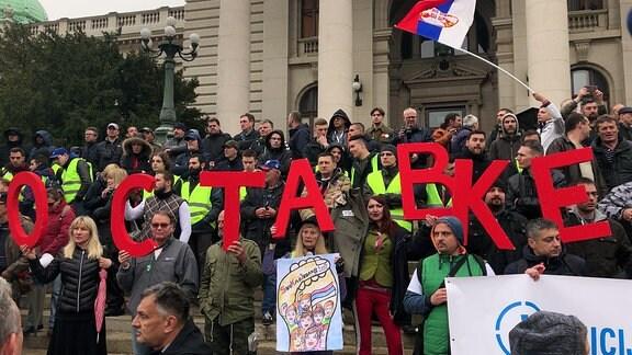 Demonstranten halten große rote Buchstaben hoch.