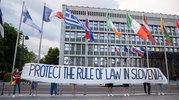 Demonstranten halten ein Banner mit der Aufschrift 'Schützt die Rechtsaatlichkeit in Slowenien'.