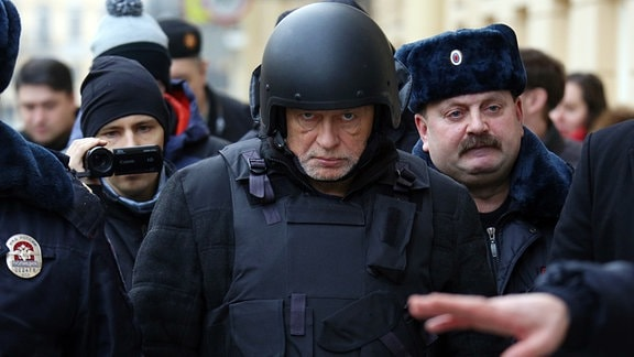 Mann in schusssicherer Weste und Helm umringt von Polizisten.