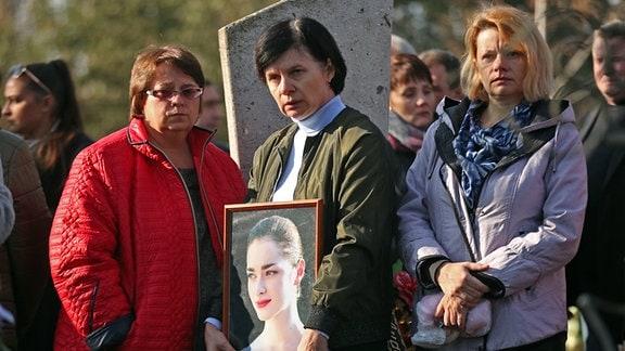 Drei frauen jalten das gerahmte Bild einer jungen Frau bei einer Beerdigung.