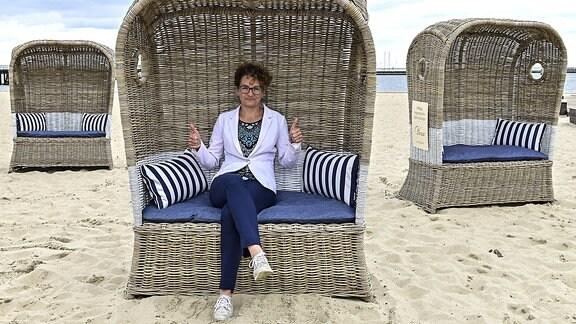 Eine Frau sitzt in einem Strandkorb und hebt die Daumen